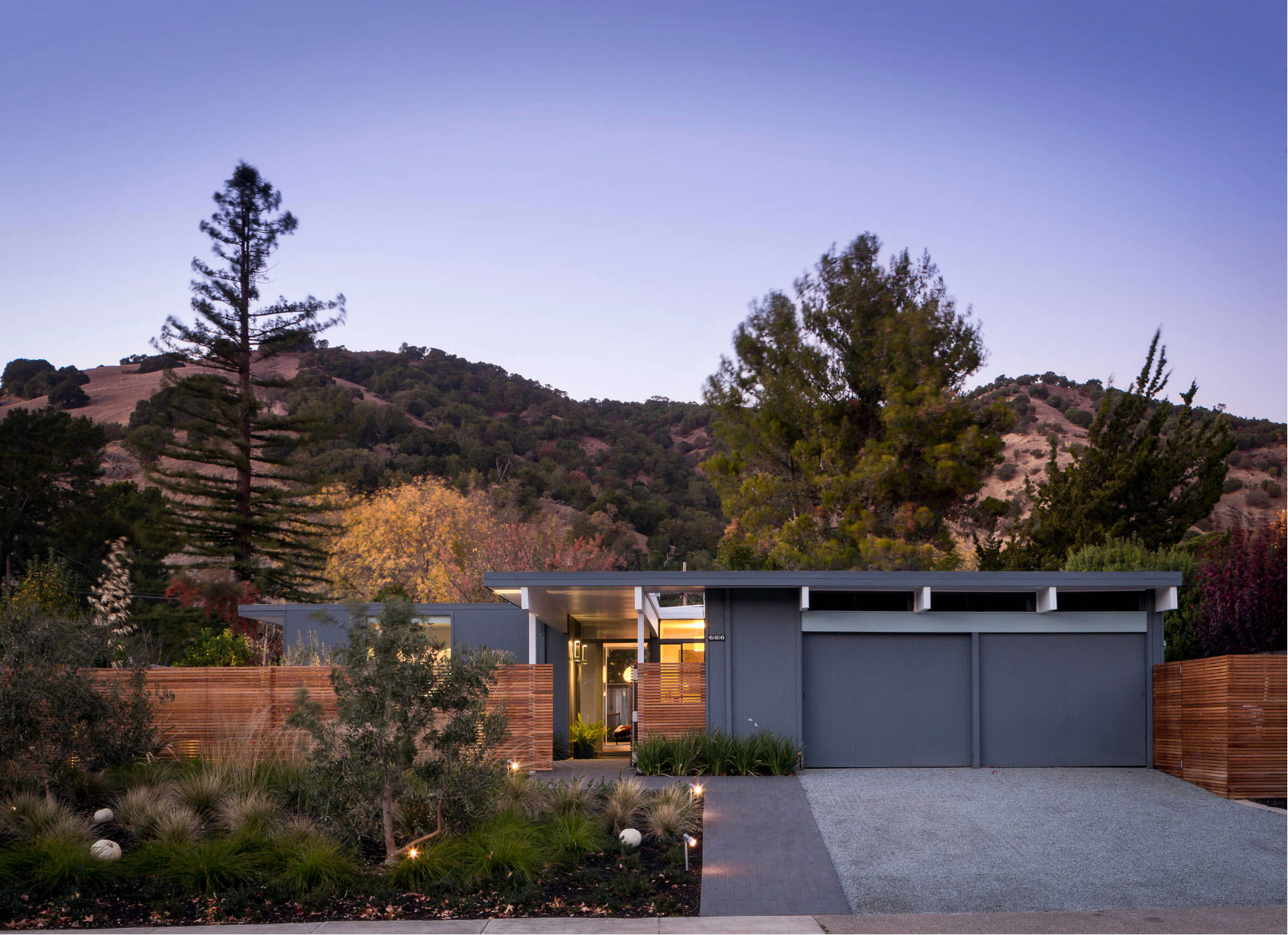 modern flat roof one-story home surrounded by trees and mountains in the background