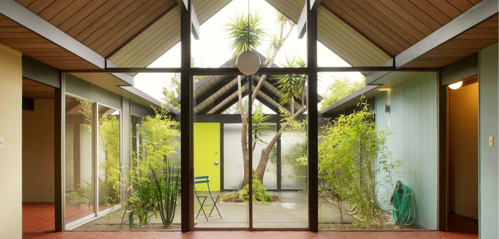 home interior with exposed beams and open-air courtyard