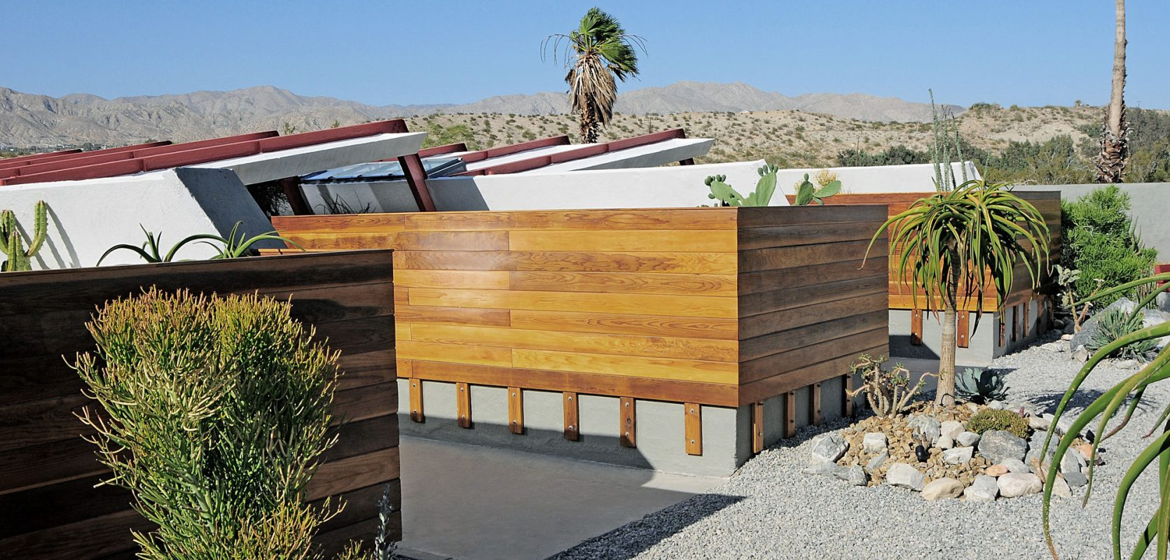 wood clad ranch style homes connected in a desert landscape and gravel drive