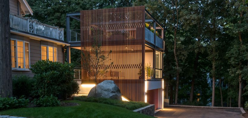 glowing 3-story garage studio steel structure with wood screen