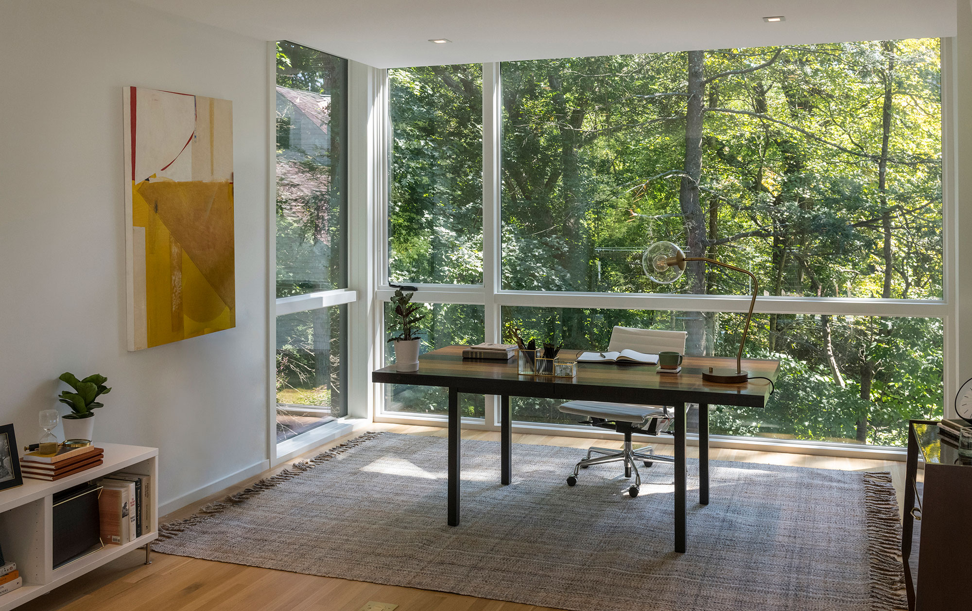 home office interior with forest view through large windows