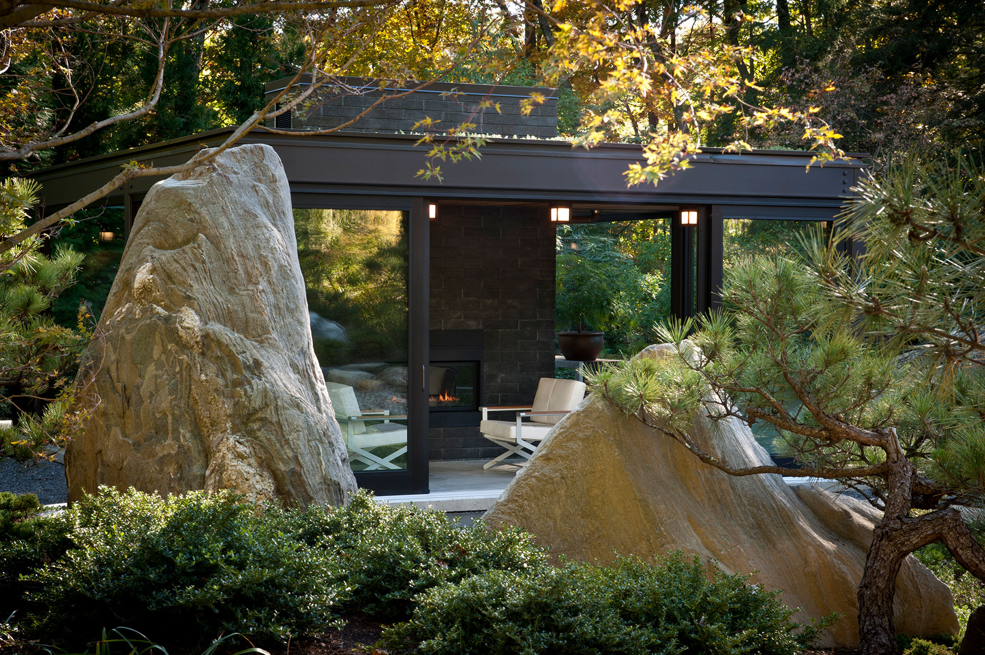 large boulder ledge in foreground with glass and steel greenhouse in background