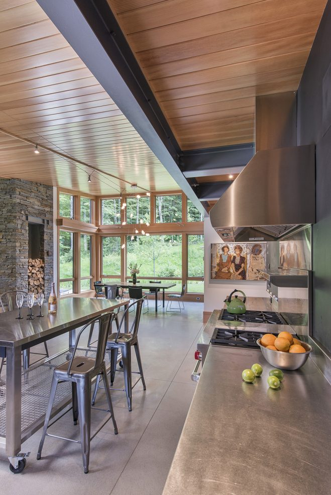 open layout of living kitchen and dining room with exposed steel