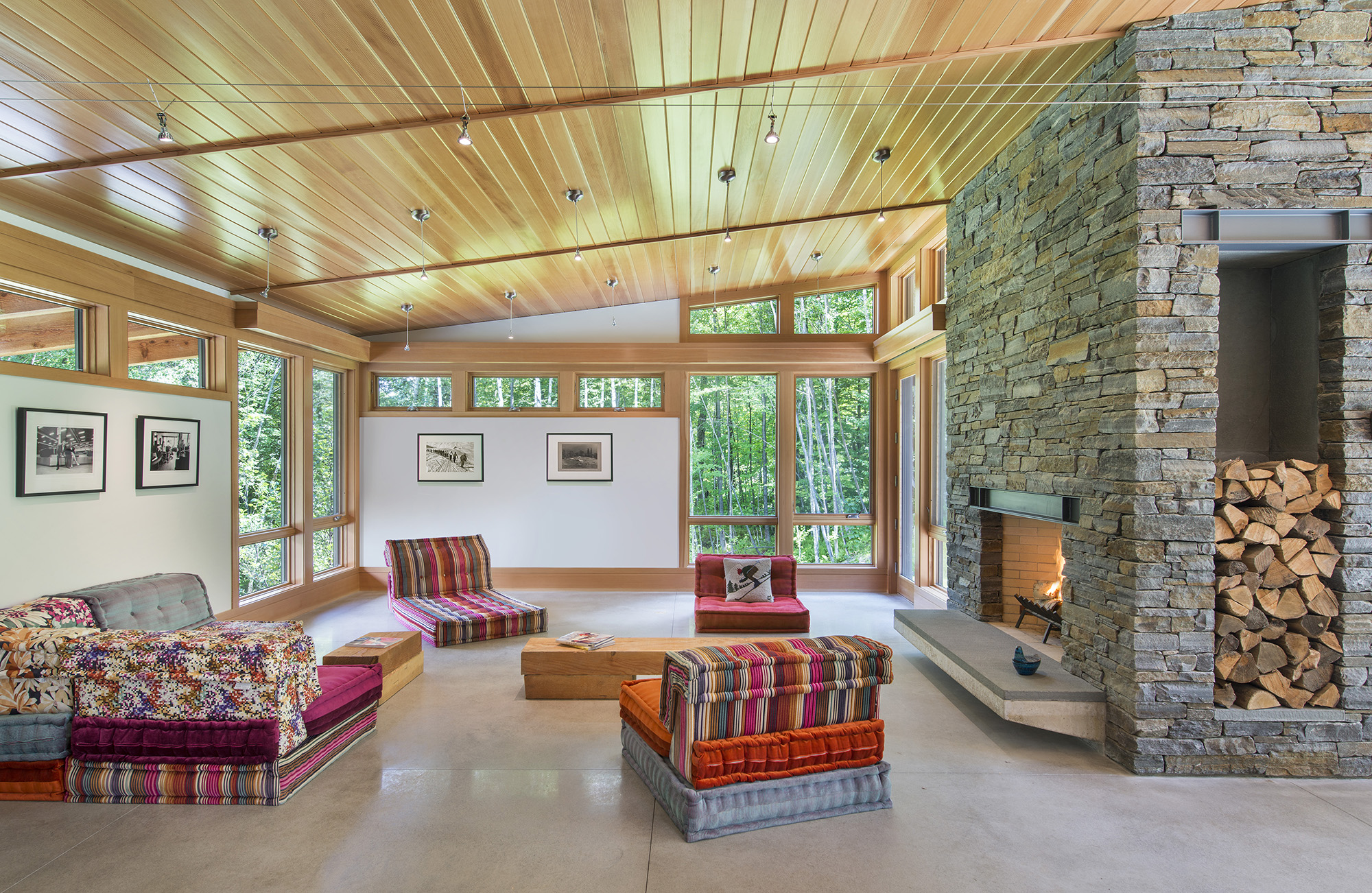 ski chalet living room with wood ceiling and large stone fireplace