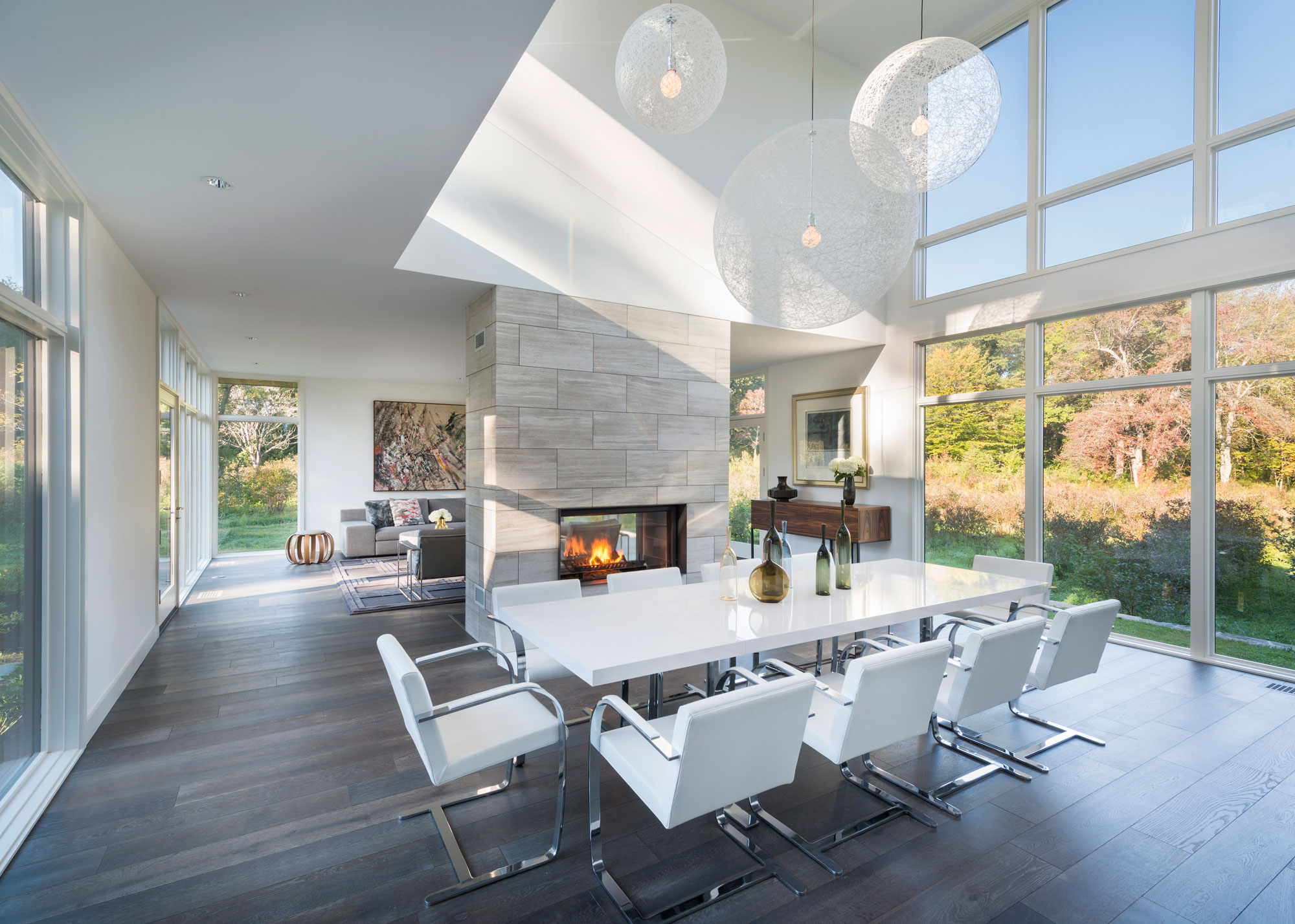 modern dining room with two-sided gas fireplace and 2-story glass windows