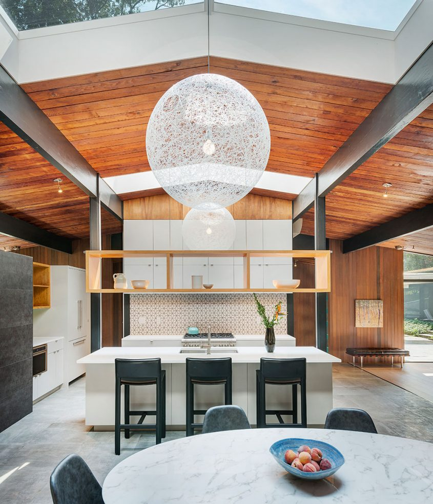 mid-century modern kitchen with large skylights and floating shelving