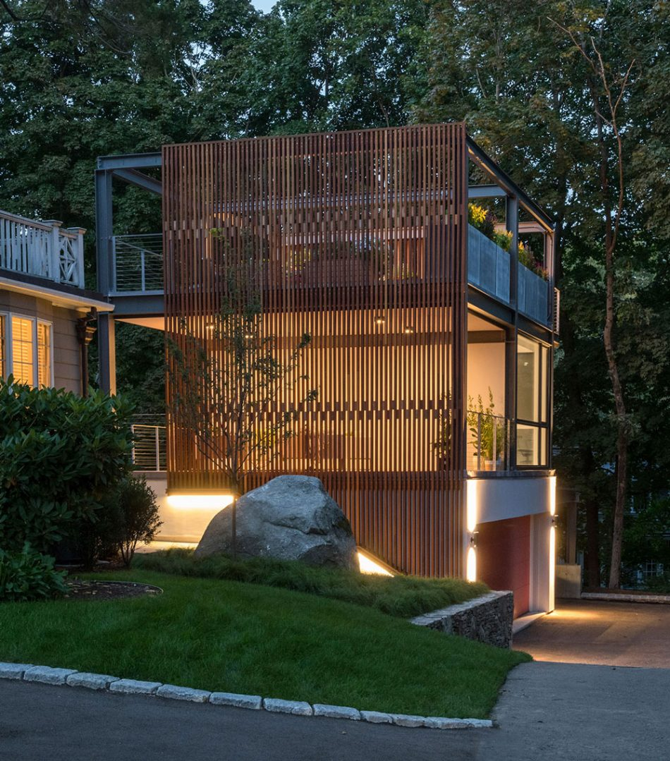 3-story studio and garage glowing at dusk