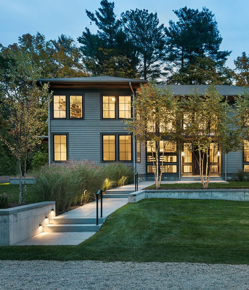 modern exterior home glowing at dusk with birch trees in the foreground