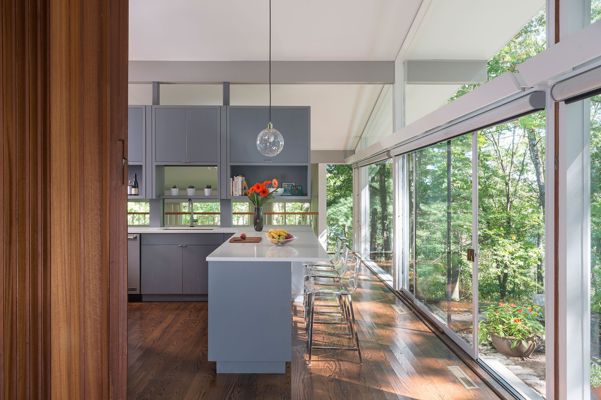 mid-century modern kitchen with floating cabinets and glass walls