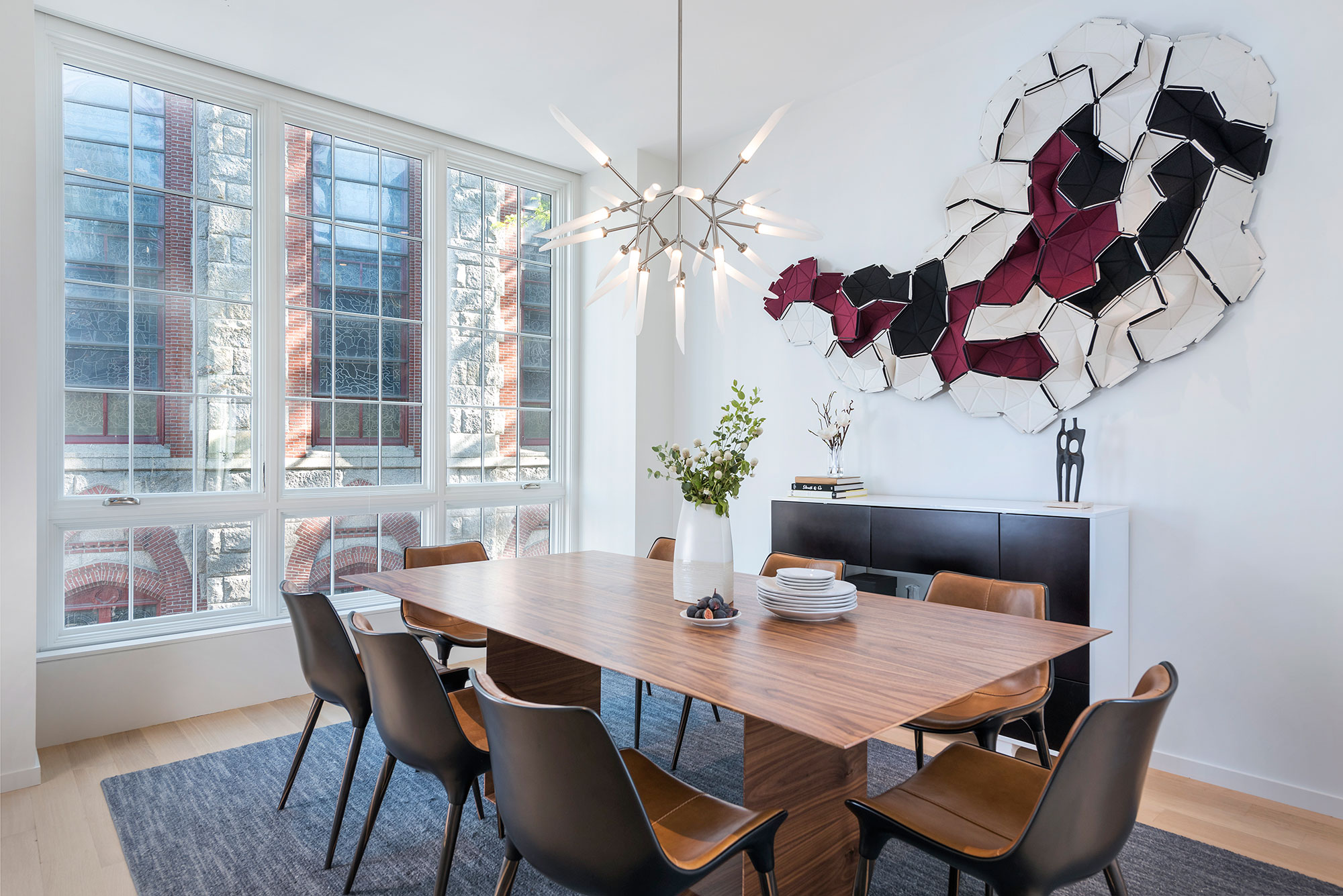 dining room with wall sculpture and modern chandelier