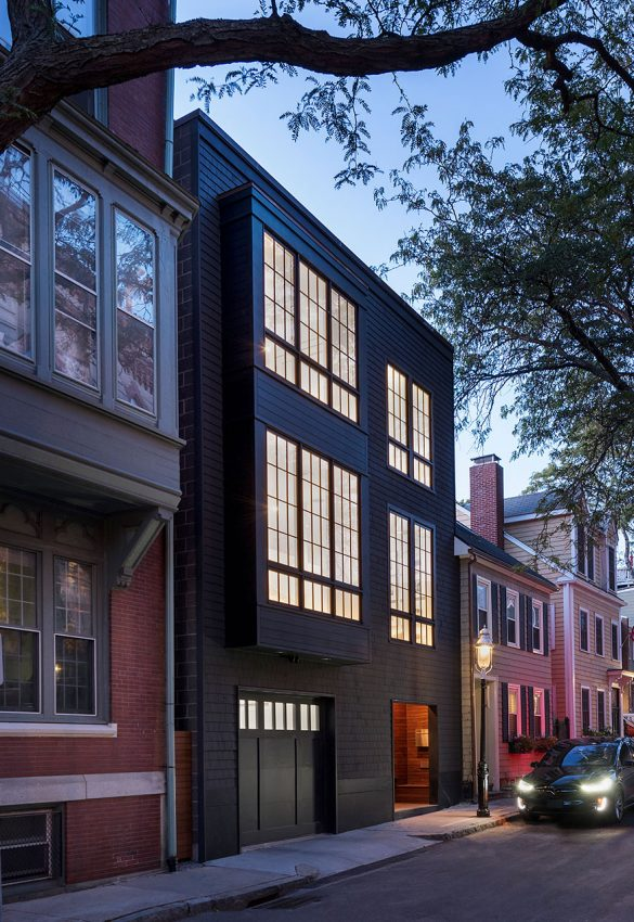 modern exterior of black 3-story row house glowing at dusk