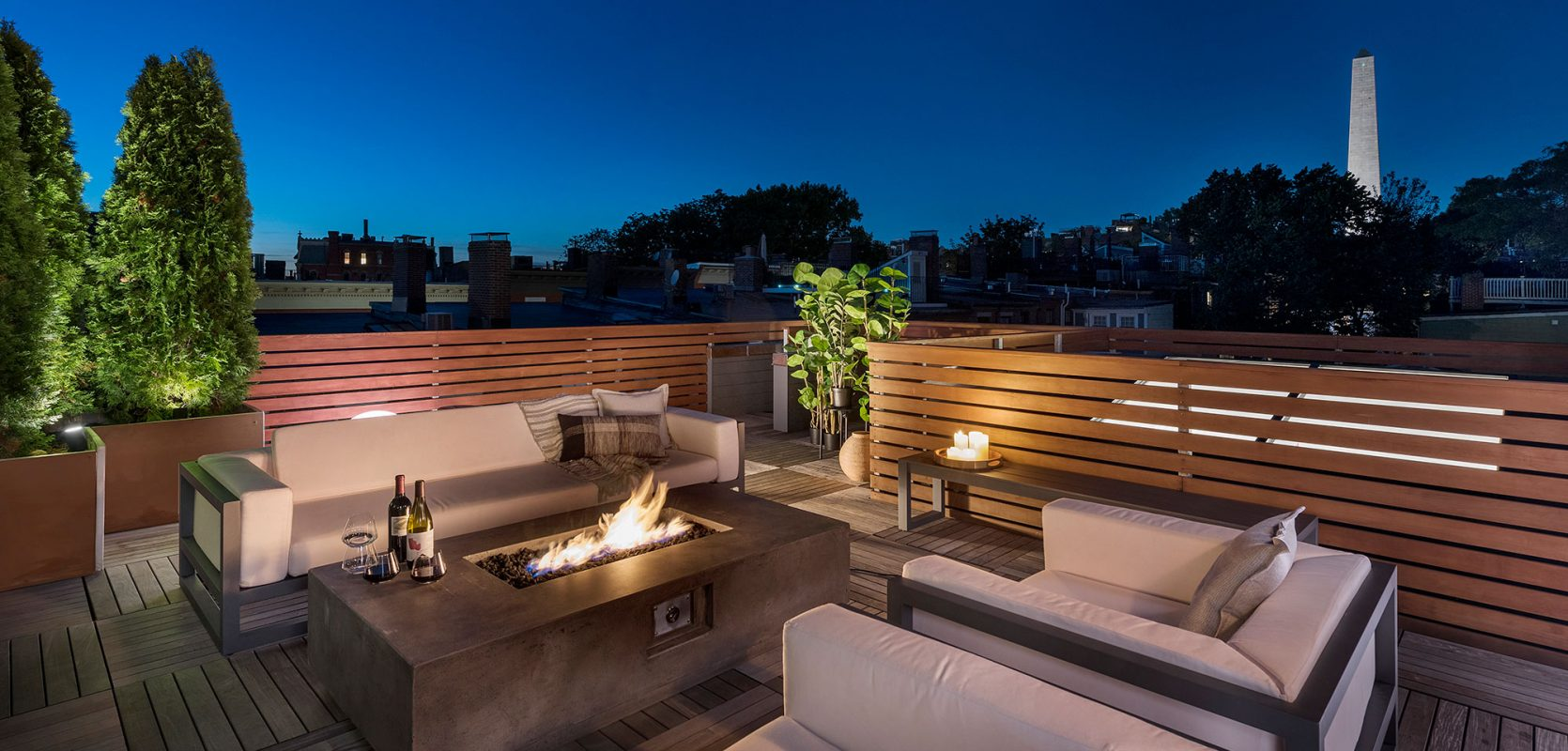 furnished rooftop of row house with gas firepit at dusk
