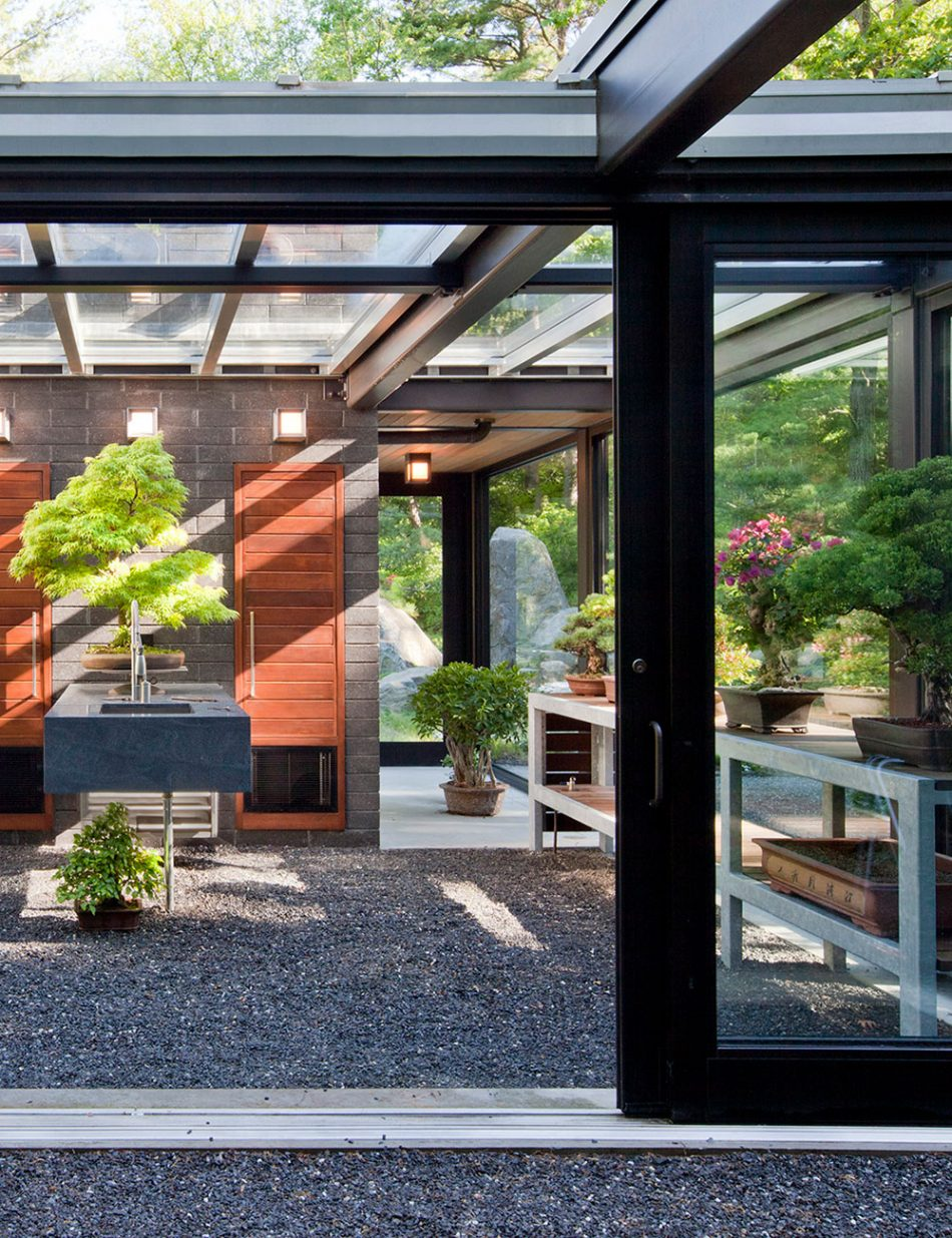 glass and steel structure with metal benches topped with bonsai's