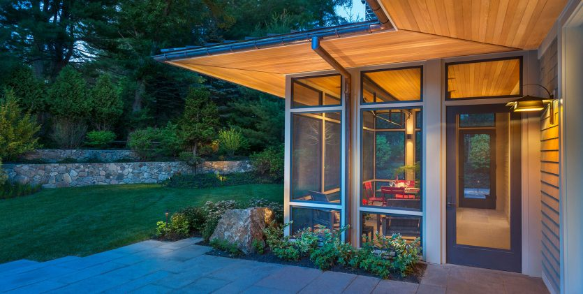 exterior corner of screen porch with extended wood soffits lit up at dusk