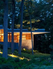 exterior corner of home glowing at night in the woods