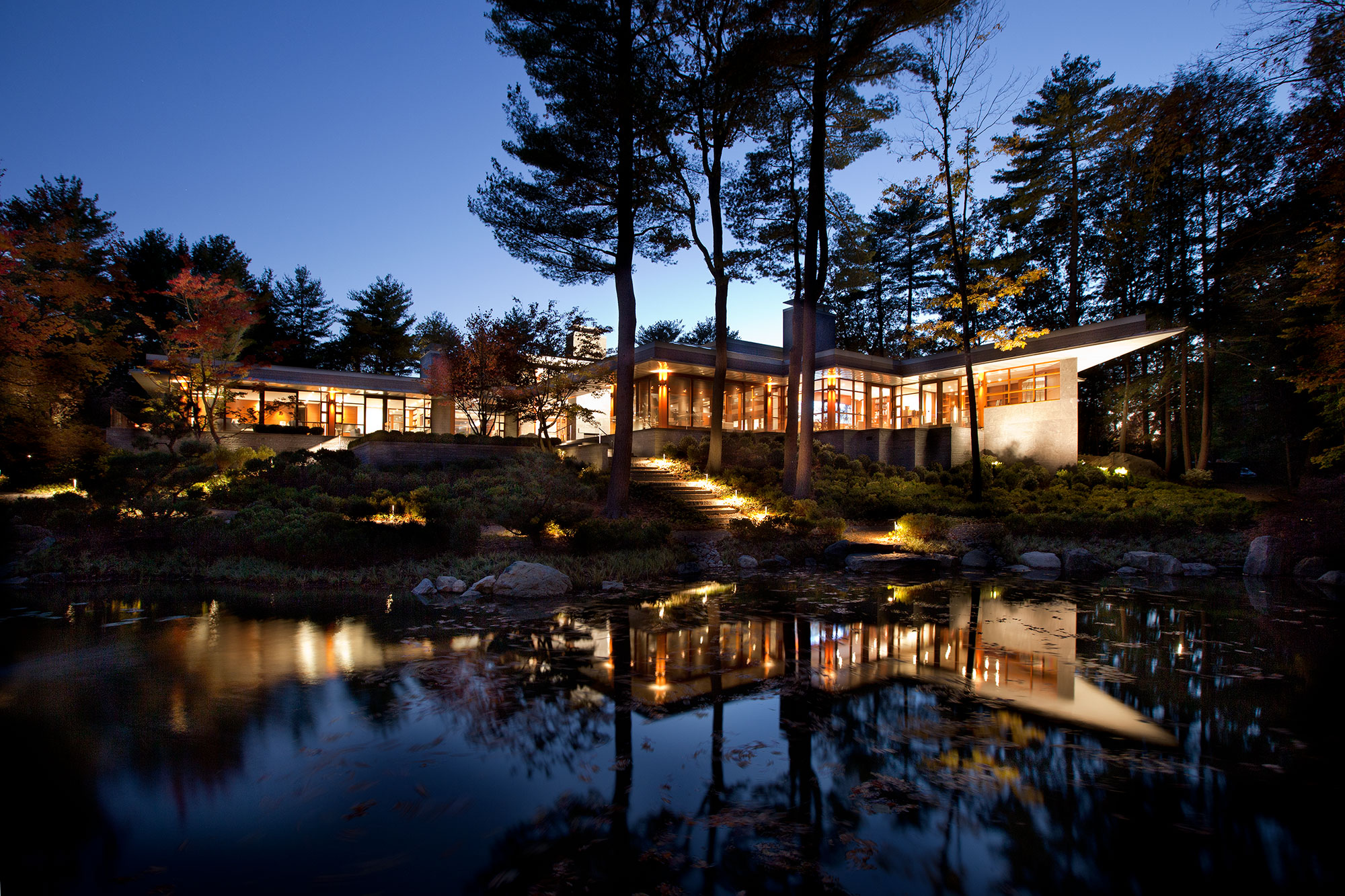 exterior of home across from a pond glowing at dusk