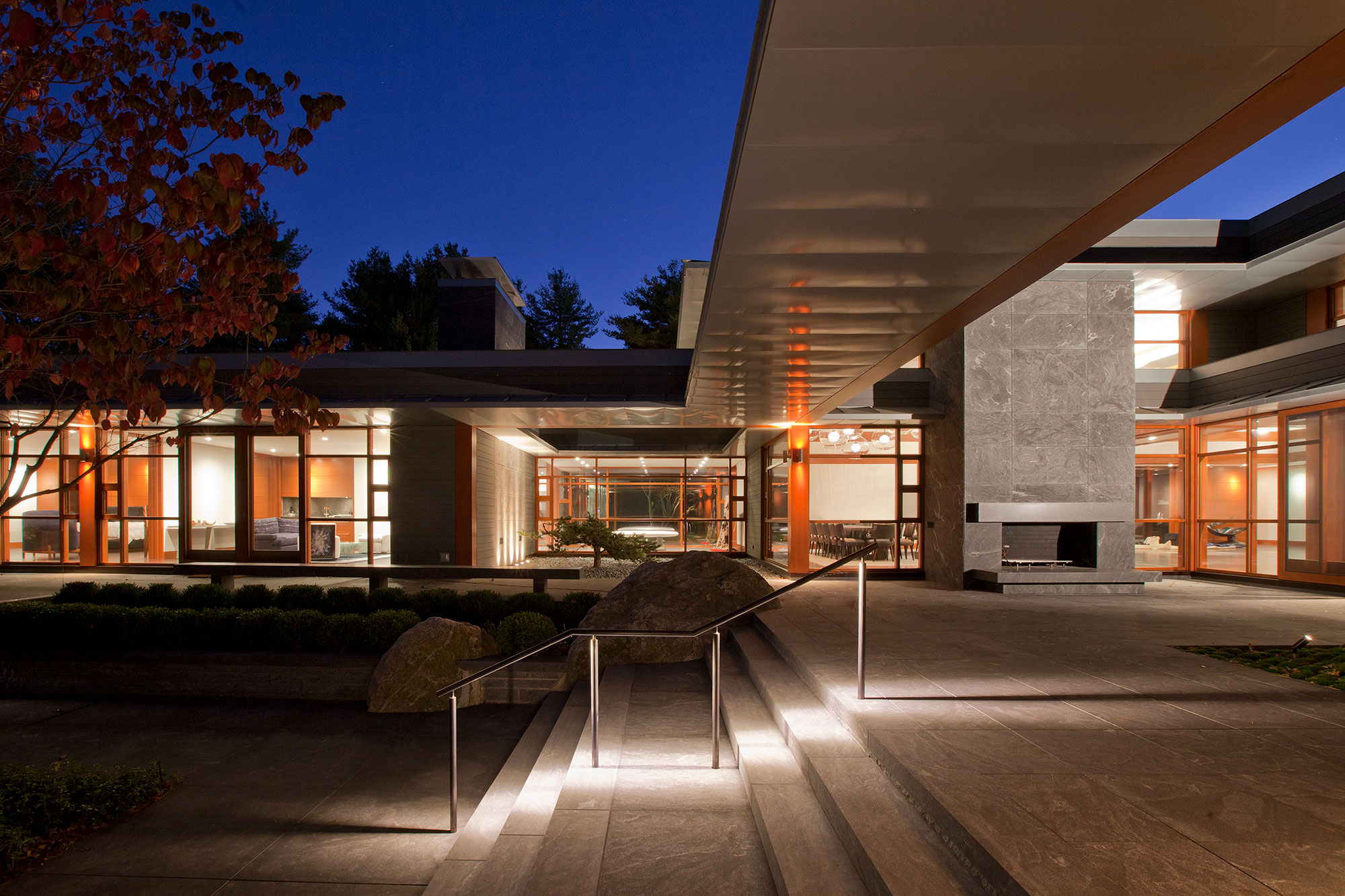 exterior of home from terrace glowing inside at dusk