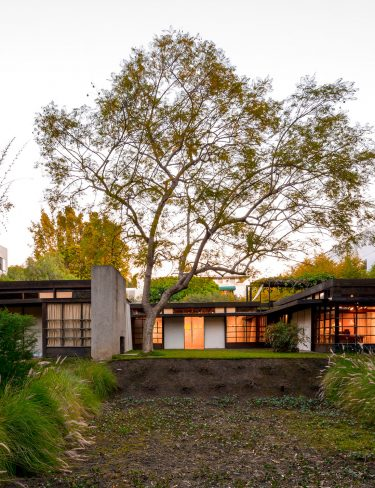 exterior of home at dusk with glowing windows surrounded by curated landscape
