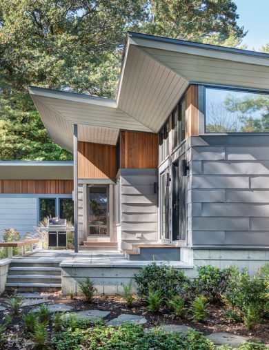 exterior of home with vertical cedar accents and warm grey metal siding