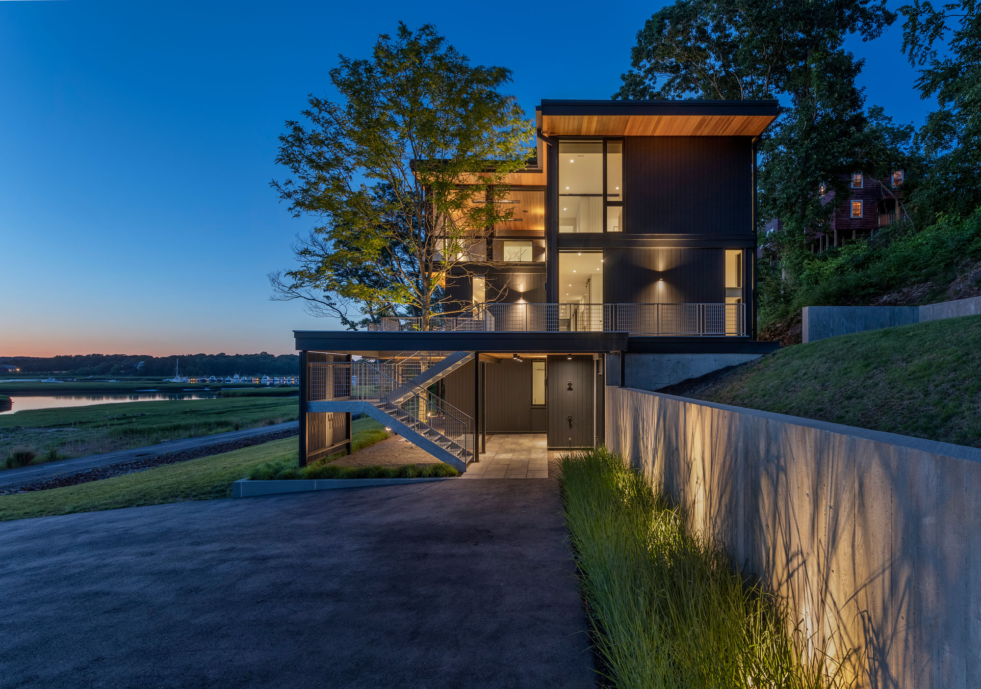 side elevation of three story home glowing at dusk overlooking tidal marsh