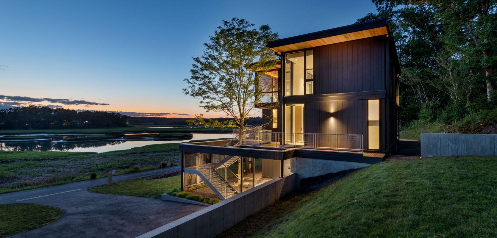 dusk shot of glowing home overlooking the marsh