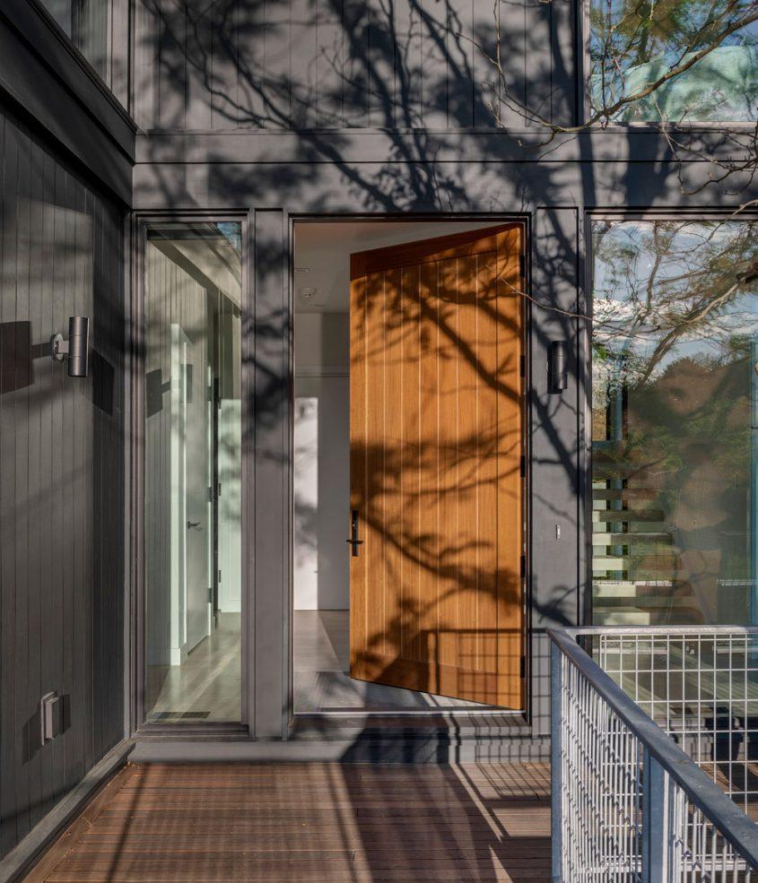 front door off second floor deck with locust tree shadow