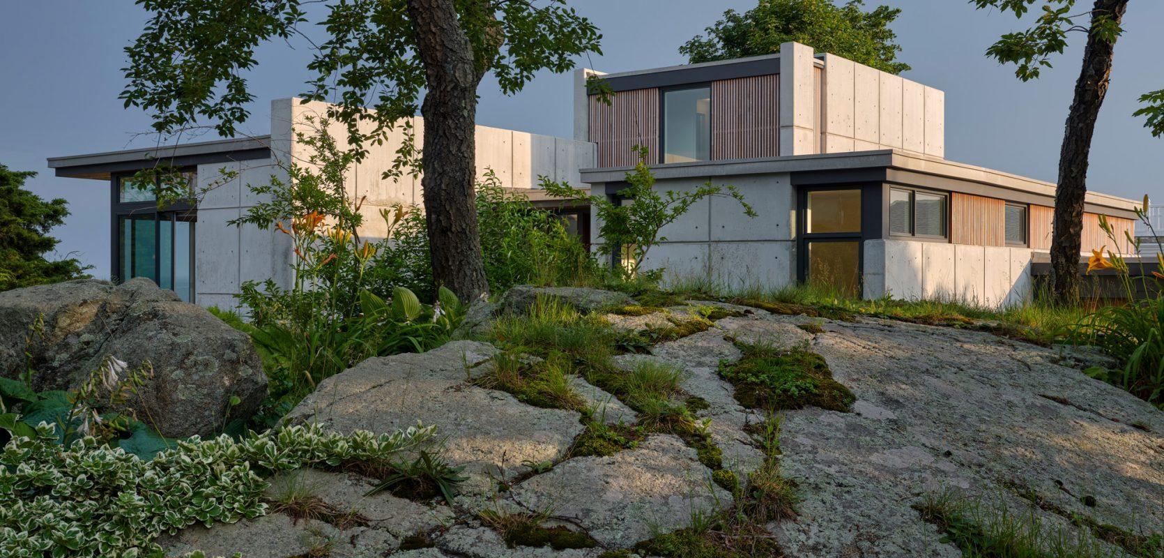 concrete home nestled into landscape with ledge