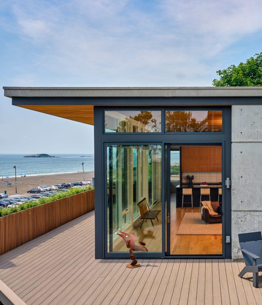 rear corner of home with deck overlooking ocean
